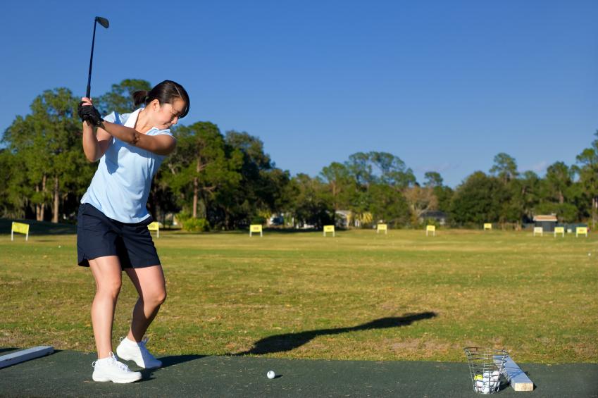 Female golfer practicing at driving range