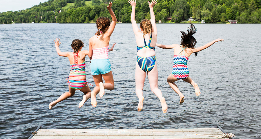 Friends jumping into water